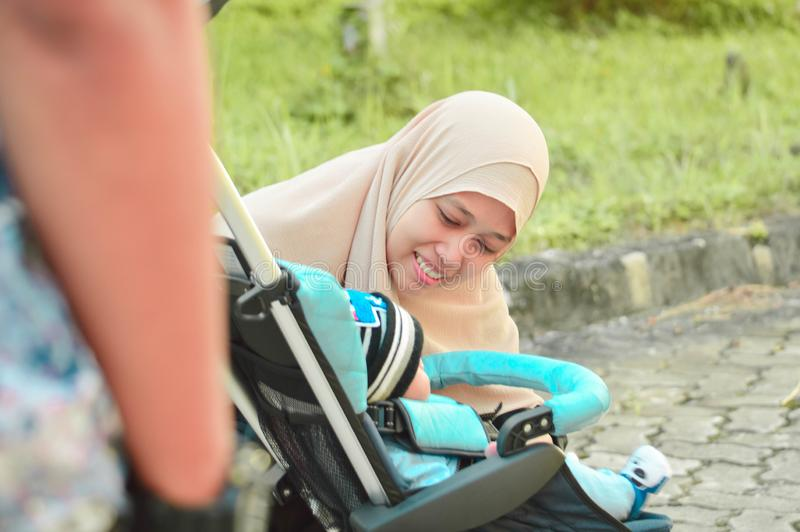 Azjatycka muzułmańska hijabi matka, ojciec i chodzimy przez parka z synem w spacerowiczu podczas gdy jego mama bierze opiekę jej  zdjęcie royalty free