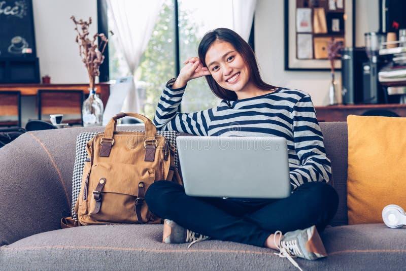 Azjatycka nastolatek dziewczyna u?ywa laptop i s?uchaj?c? muzyk? na kanapie z szcz??liw? u?miechni?t? twarz? przy sklep z kaw?, w obraz royalty free