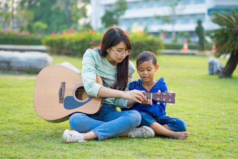Azjatycka nastoletnia dziewczyna uczy gitarę dla chłopiec z czule i fu obrazy royalty free