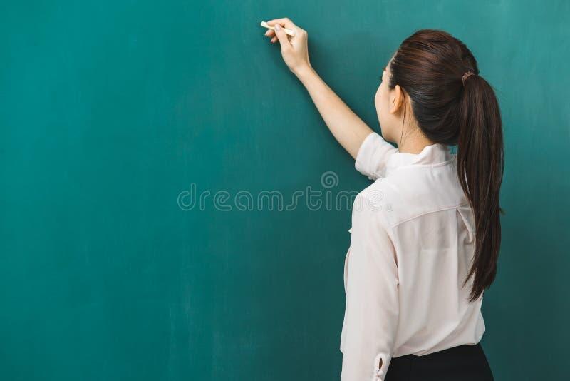 Azjatycka nauczyciel kreda na zieleni desce zdjęcie stock