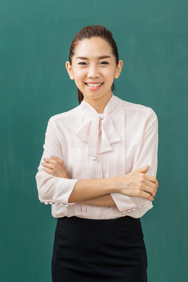 Azjatycka nauczyciel kreda na zieleni desce obrazy stock