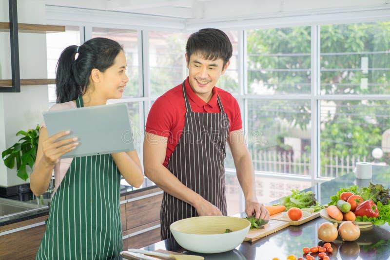 Azjatycka para gotuje w kuchni M??czyzny i kobiety u?miechni?ty przygl?daj?cy menu od pastylki M??czyzna jest tn?cymi warzywami z obrazy stock