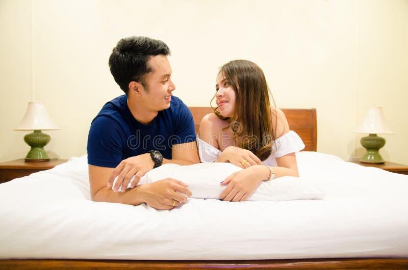 Azjatycka para kłama wpólnie na łóżku i opowiadać fotografia royalty free