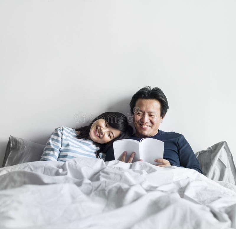 Azjatycka para relaksuje na łóżku wpólnie zdjęcia stock