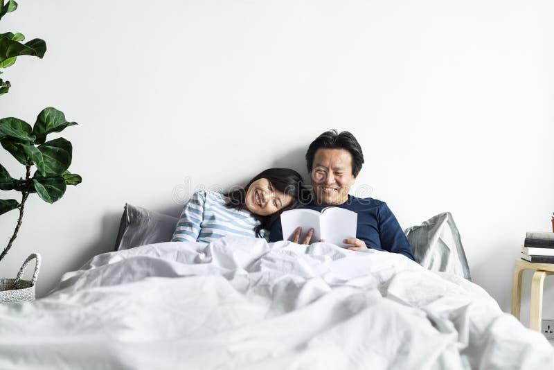 Azjatycka para relaksuje na łóżku wpólnie zdjęcie stock