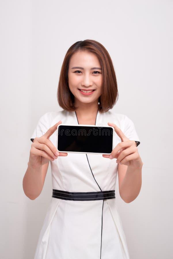 Azjatycka piękna biznesowa kobieta trzyma białego telefon komórkowego z pustym czerń ekranem i pokazuje zdjęcia stock