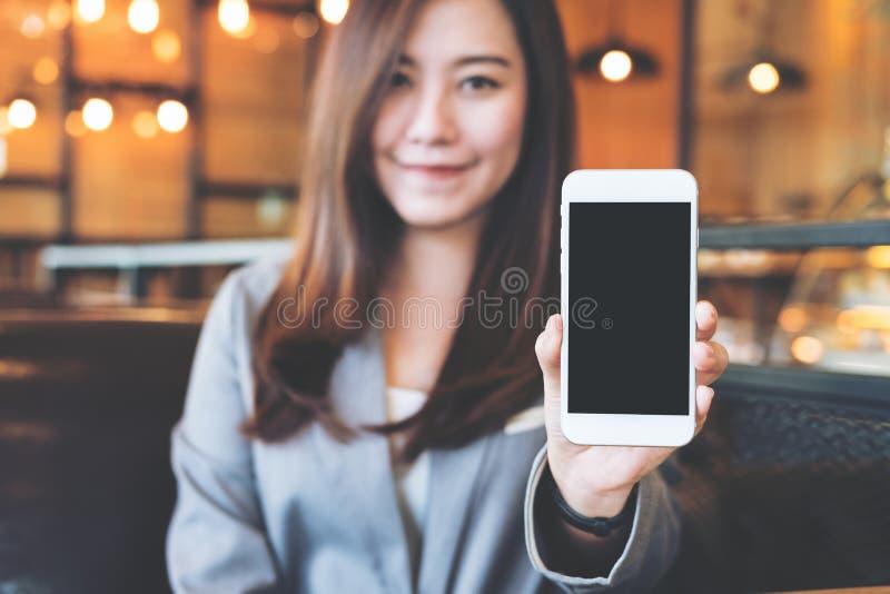 Azjatycka piękna biznesowa kobieta trzyma smiley twarz i pokazuje białego telefon komórkowego z pustym czerń ekranem w kawiarni i obraz stock