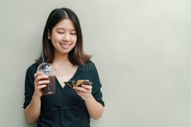 Azjatycka piękna kobieta Jest ubranym czarną koszula, stoi pijący zimną kawę w ręce I kartę kredytową w ręki Szczęśliwej twarzy fotografia stock