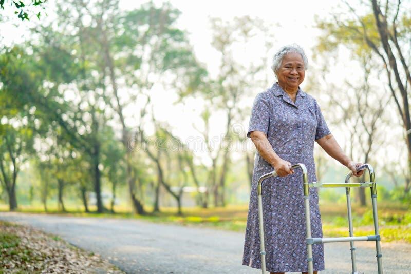 Azjatycka pielęgniarki physiotherapist lekarki opieka, senior lub starszej starej damy kobiety cierpliwy spacer z piechurem przy  obrazy stock