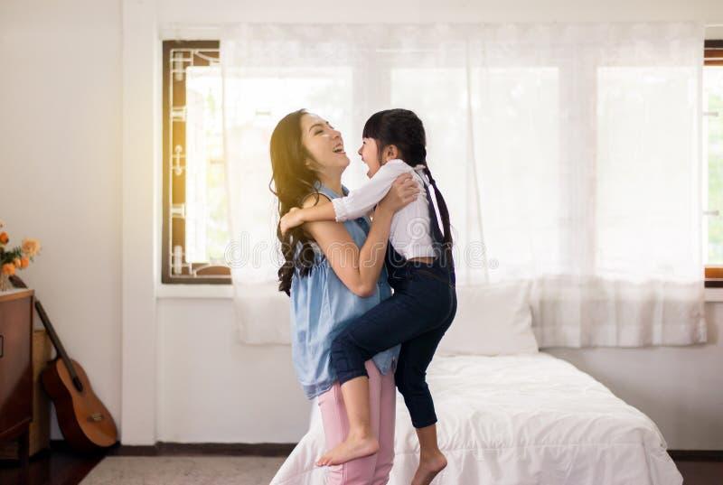 Azjatycka pojedyncza mama niesie jej rozochoconej córki w domu, Szczęśliwy i śmieszny, zdjęcia stock