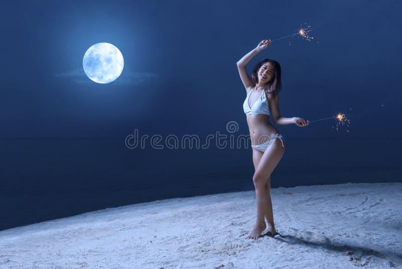 Azjatycka seksowna dziewczyna w bikini mienia fajerwerkach na plaży przy nocą obrazy stock