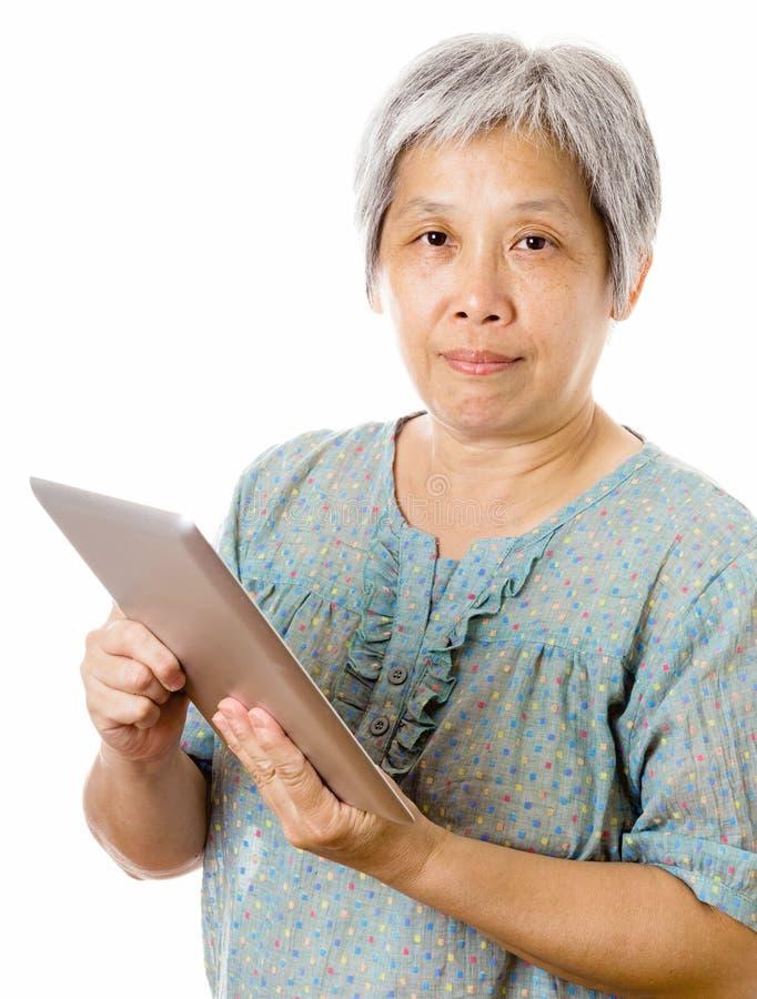 Azjatycka stara kobieta używa pastylkę obrazy stock