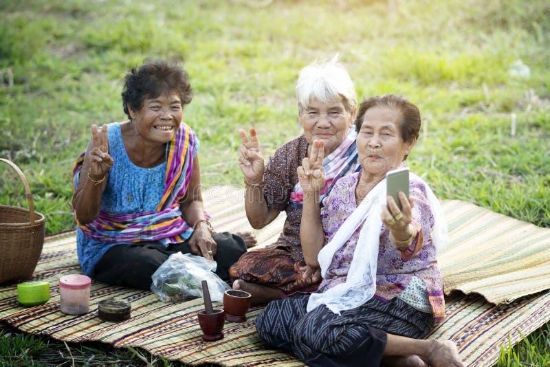 Azjatycka stara kobieta używa telefon komórkowego fotografia royalty free