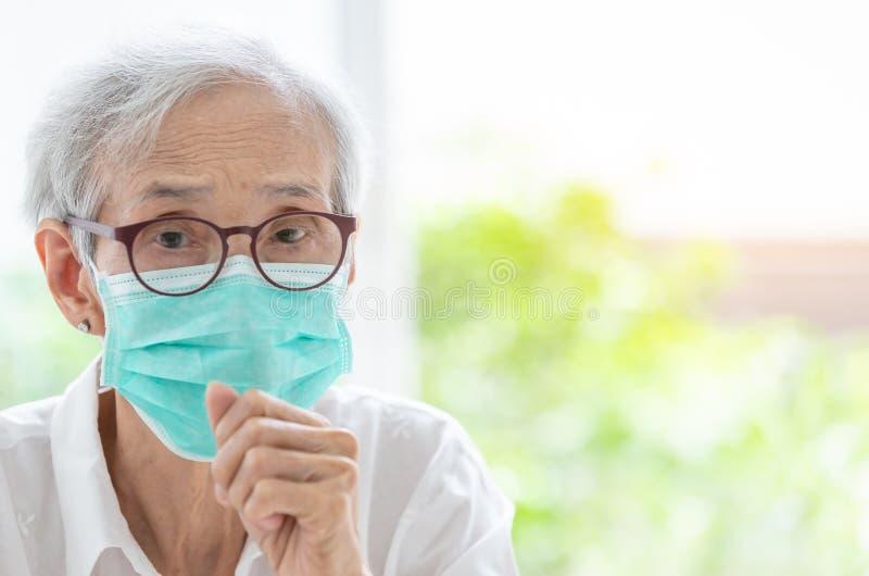 Azjatycka starsza kobieta cierpi od kasłania z twarzy maski ochroną, starsza kobieta jest ubranym twarzy maskę przez zanieczyszcz obraz stock