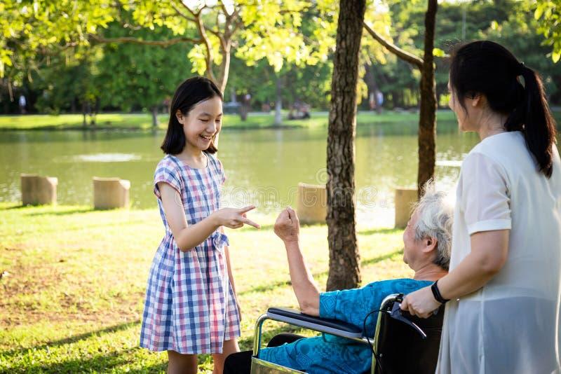 Azjatycka starsza kobieta gra w rock papierową nożyczkę, ma szczęście, uśmiecha się z córką i wnuczką na wózku inwalidzkim fotografia royalty free