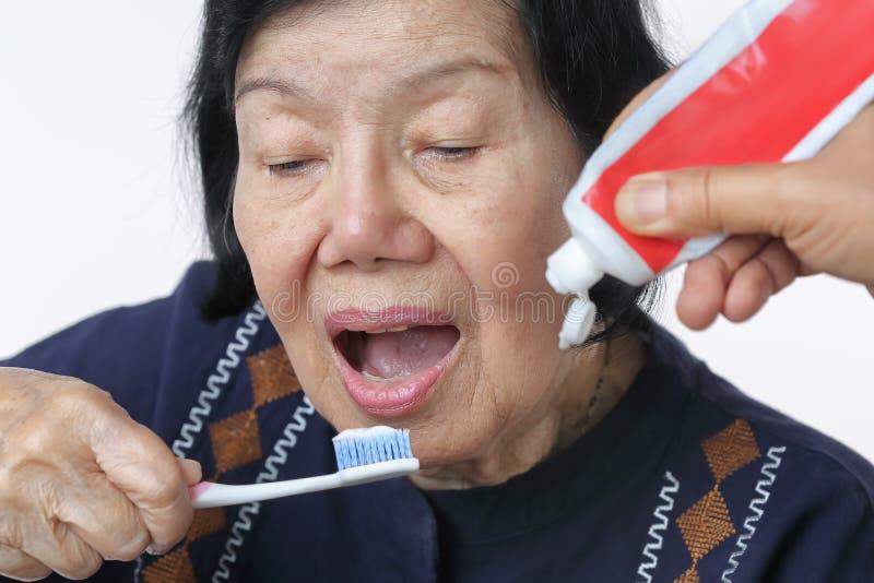 Azjatycka starsza kobieta próbuje use toothbrush, ręki drżenie obrazy royalty free