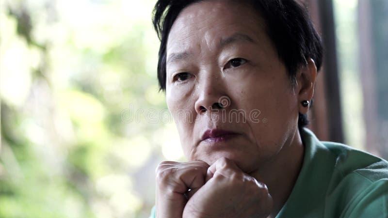 Azjatycka starsza kobieta z ręką na twarzy główkowaniu, martwi się smutnego obrazy stock