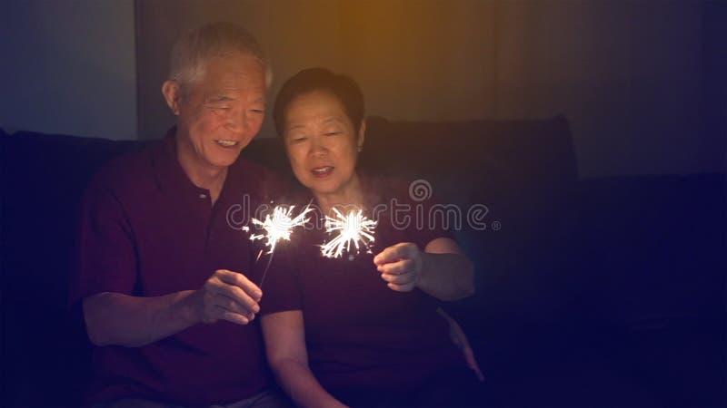 Azjatycka starsza para świętuje wpólnie w domu błyska fajerwerk s obrazy royalty free