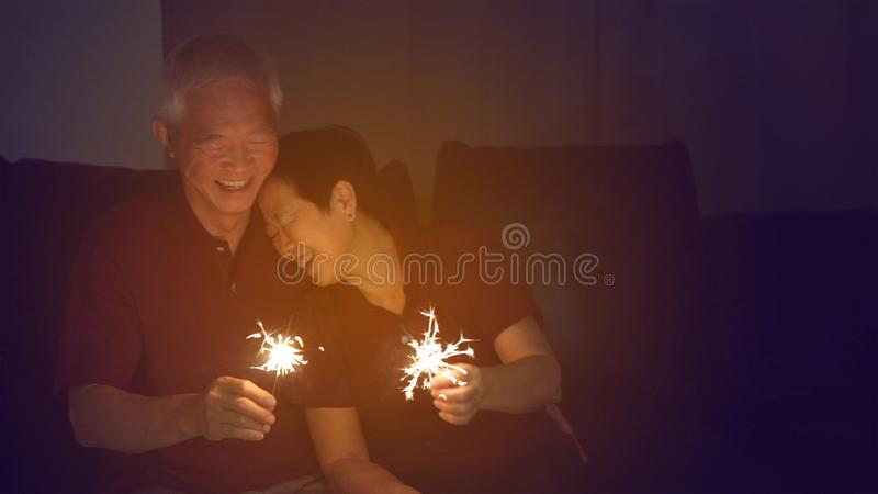 Azjatycka starsza para świętuje wpólnie w domu błyska fajerwerk s obraz royalty free