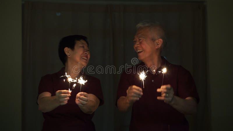 Azjatycka starsza para bawić się sparklers, pożarniczy krakers przy nocą Pojęcie odświętności życie obrazy stock