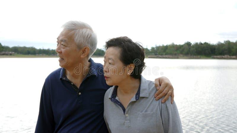 Azjatycka starsza para szczęśliwa ściskający wpólnie jeziornego tło zdjęcie royalty free