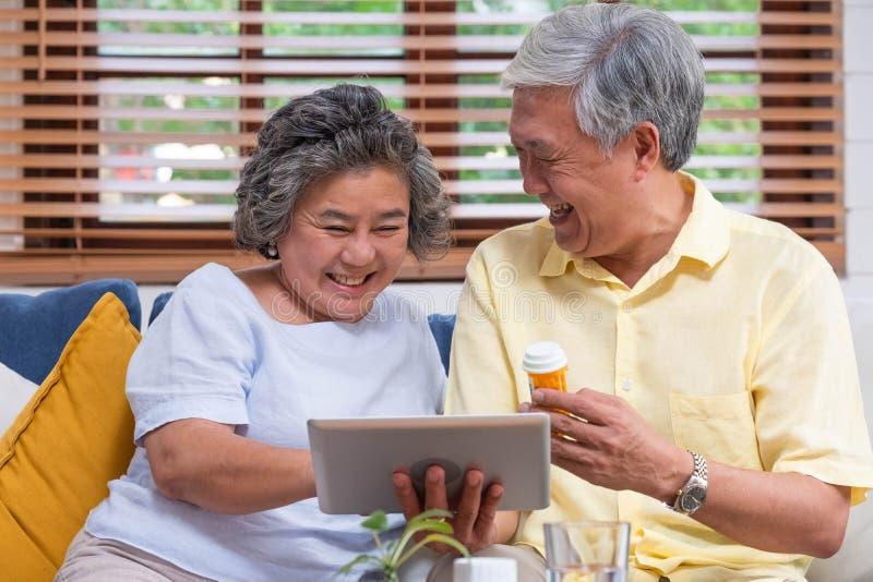 Azjatycka starsza para używa pastylki wideokonferencję z lekarką o pigułce uczy się używać podczas gdy siedzący na kanapie w domu zdjęcia royalty free