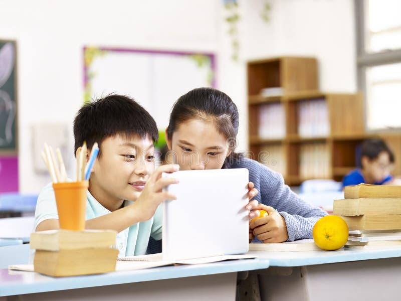 Azjatycka szkoły podstawowej dziewczyna i uczniowska używa pastylka wpólnie obraz royalty free