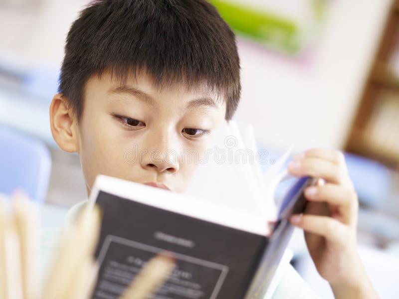 Azjatycka szkolna chłopiec czyta książkę zdjęcie stock