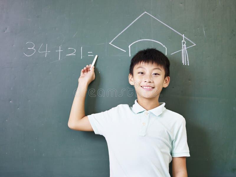 Azjatycka uczniowska pozycja pod rysującym doktorskim kapeluszem zdjęcie stock