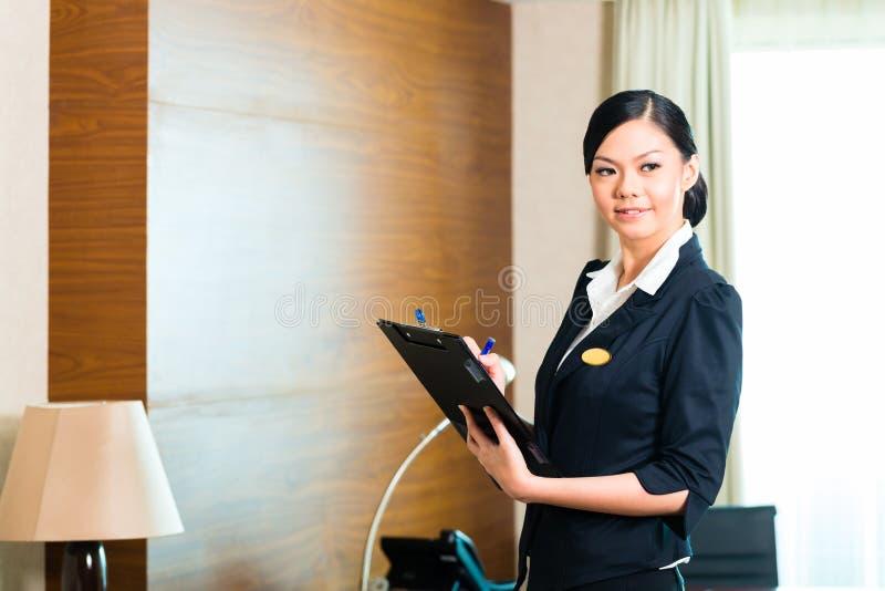 Azjatycka wykonawcza gospodyni kontroluje pokój hotelowego obraz stock