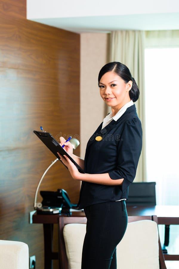 Azjatycka wykonawcza gospodyni kontroluje pokój hotelowego obrazy stock