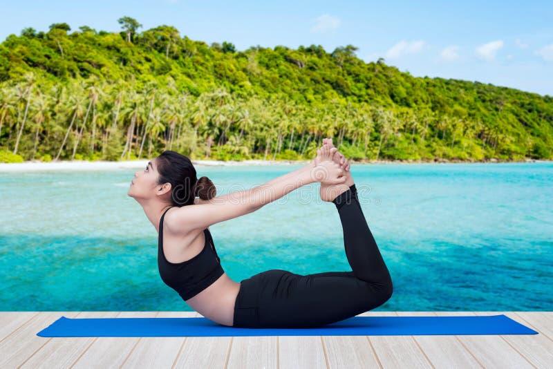 Azjatycka zdrowa kobieta cieszy się ćwiczy joga pozę przy tropikalnym morzem obrazy royalty free