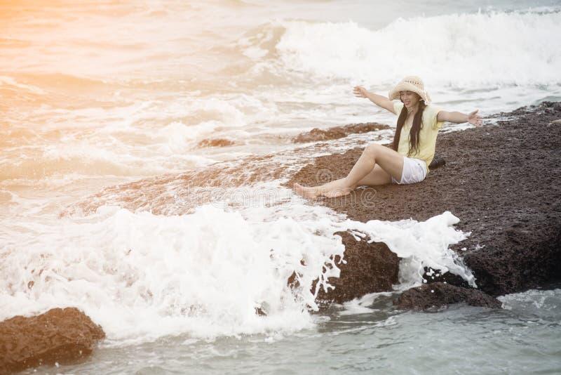Azjatycki ładny żeński obsiadanie na skałach z silnym fali i relaksu szczęściem obraz stock