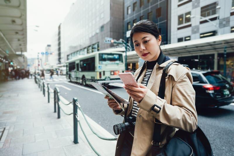 Azjatycki żeński turysta używa online miasto przewdonika fotografia royalty free