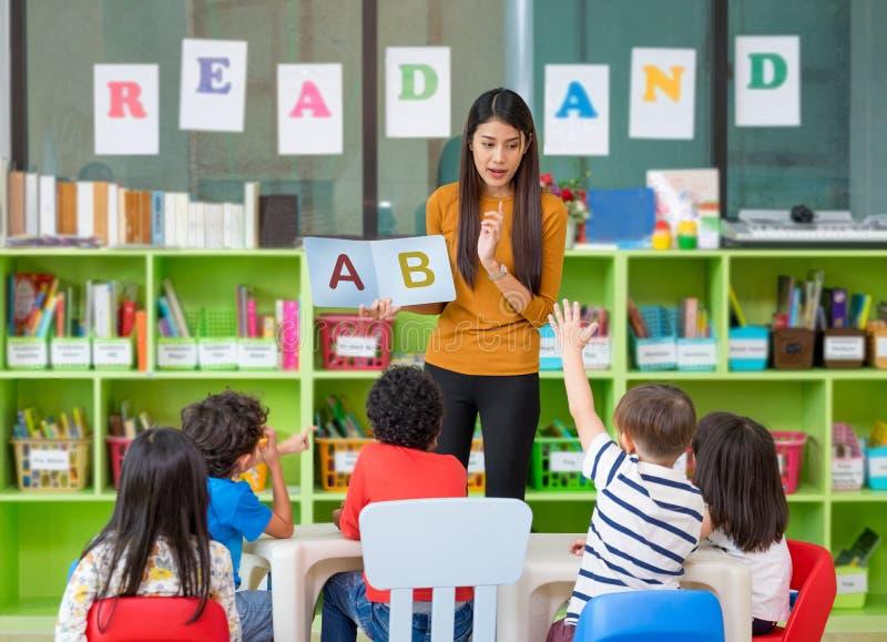 Azjatycki żeńskiego nauczyciela nauczanie i pytać mieszających biegowych dzieciaków wręczamy up obrazy royalty free