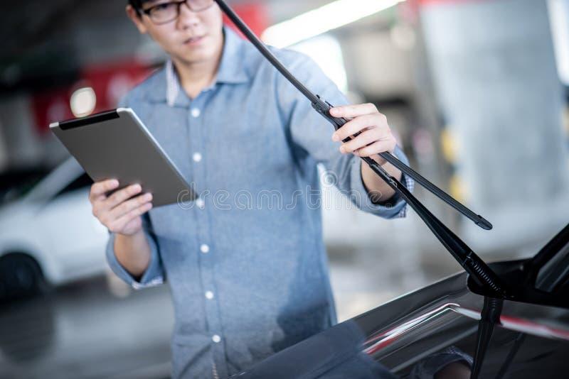 Azjatycki auto mechanik sprawdza przedniej szyby wiper obraz stock