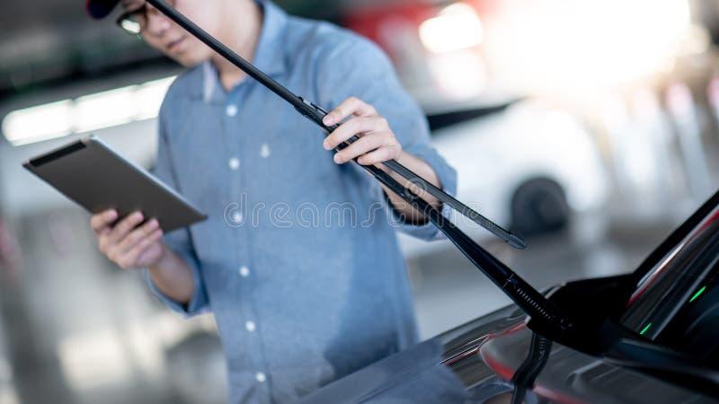 Azjatycki auto mechanik sprawdza przedniej szyby wiper obraz royalty free