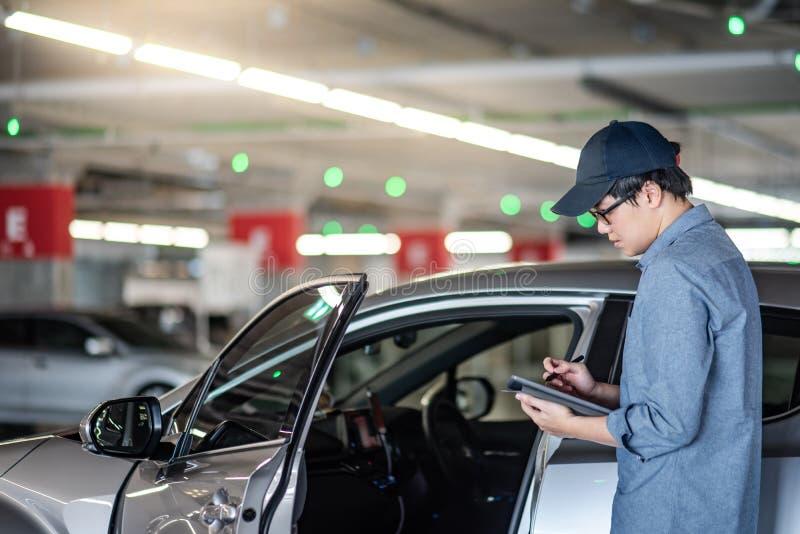 Azjatycki auto mechanik sprawdza samochodową używa pastylkę obrazy stock