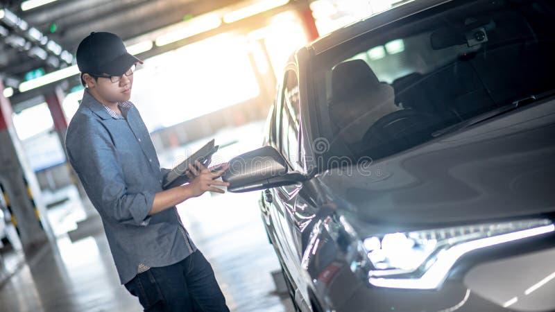 Azjatycki auto mechanik sprawdza samochodową używa pastylkę zdjęcie royalty free