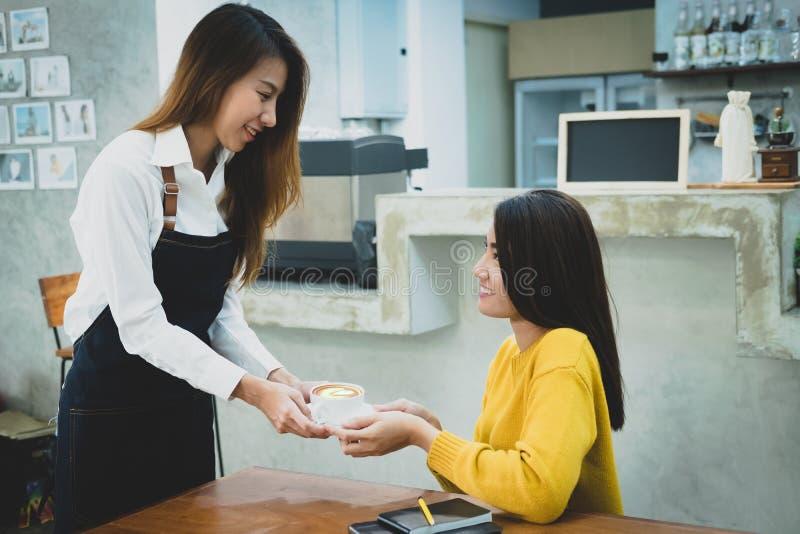 Azjatycki barista słuzyć filiżankę kawy klient Cukierniany restaura obrazy royalty free