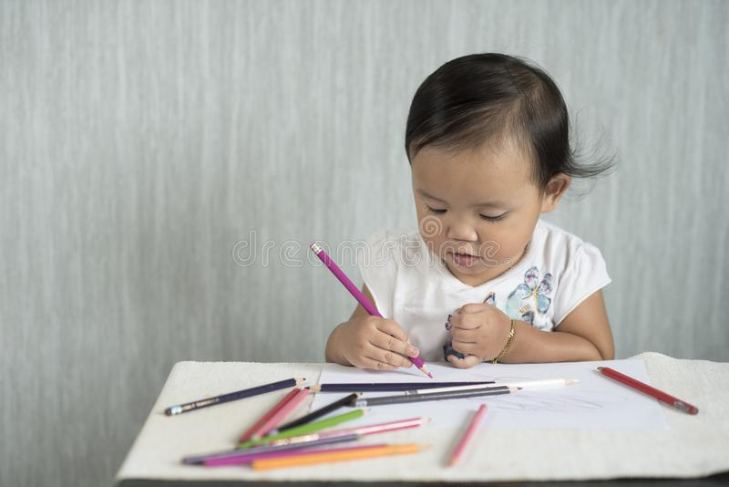 Azjatycki berbeć, dziewczynka/mamy zabawa uczenie używać ołówki zdjęcie stock
