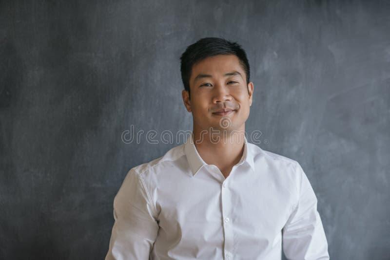 Azjatycki biznesmen ono uśmiecha się podczas gdy stojący przed chalkboard zdjęcie stock