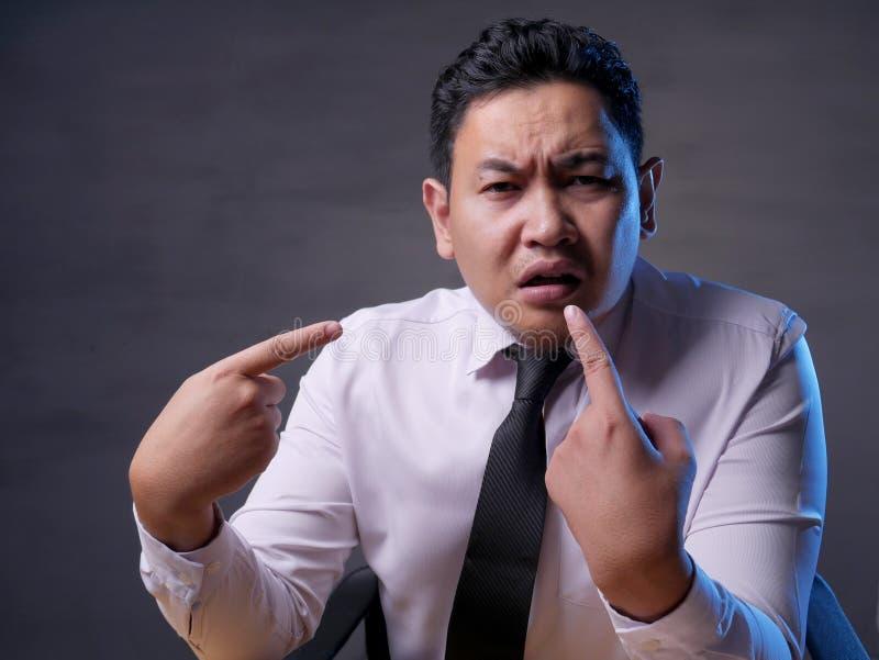 Azjatycki biznesmen ono Wskazuje z Nieszczęśliwym wyrażeniem tak jakby wprawiać w zakłopotanie być obwinionym zdjęcie royalty free