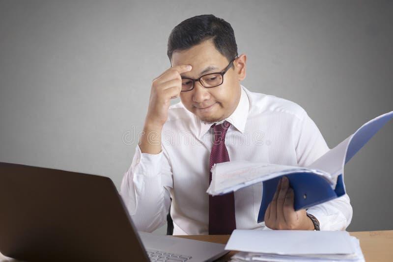 Azjatycki biznesmen Pracuje na laptopie przy Biurowym, Zm?czonym stresu gestem, fotografia royalty free