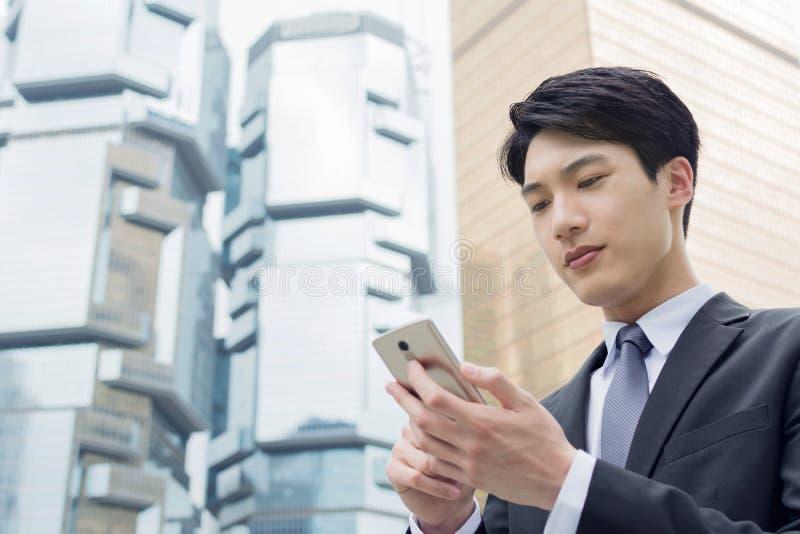 Azjatycki biznesmen używa telefon komórkowego zdjęcia stock