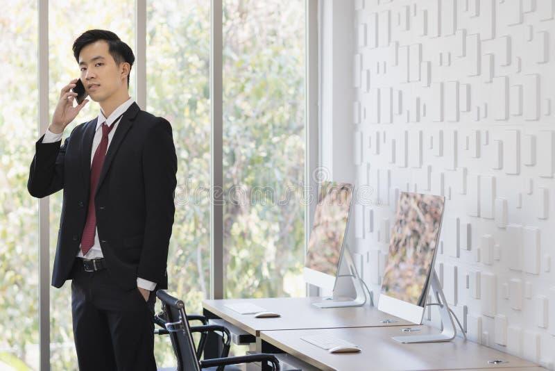 Azjatycki biznesmen u?ywa telefon kom?rkowego w biurze obraz stock