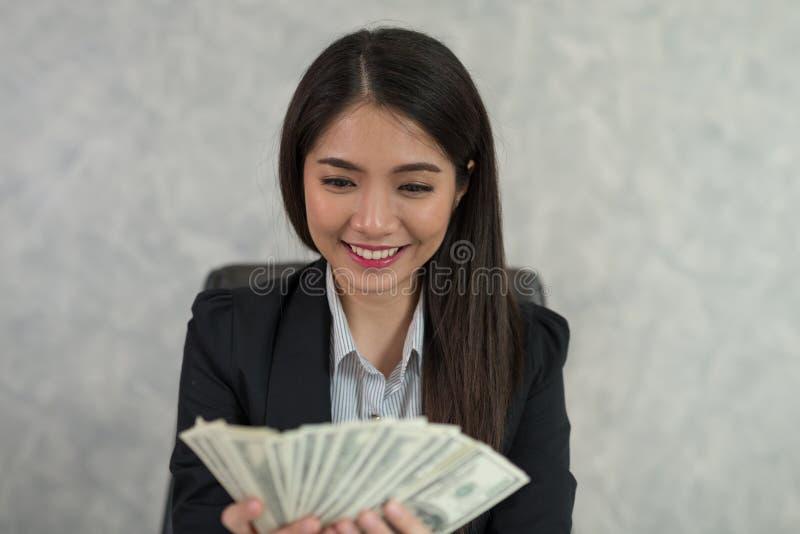 Azjatycki biznesowej kobiety mienia pieniądze w ręce i ono uśmiecha się szczęśliwych obrazy stock
