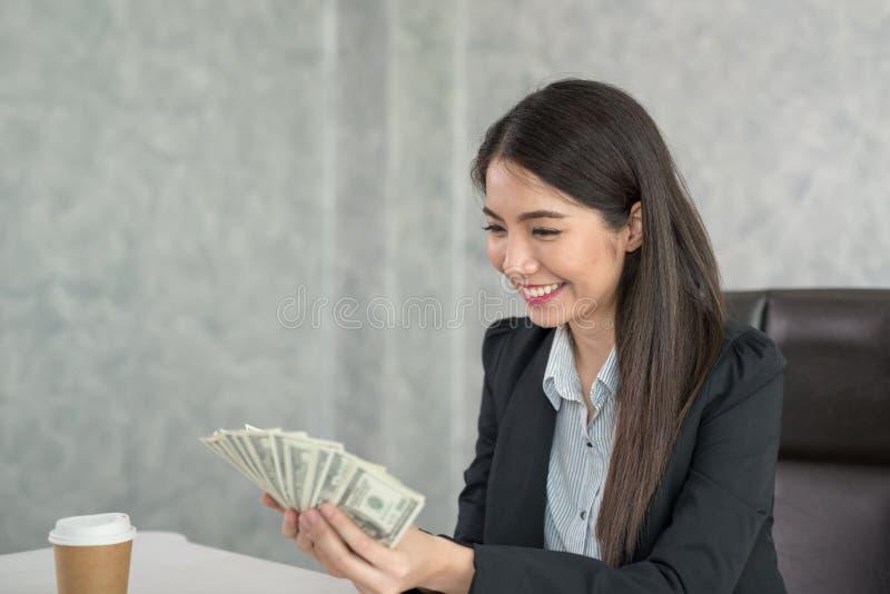 Azjatycki biznesowej kobiety mienia pieniądze w ręce i ono uśmiecha się szczęśliwych fotografia royalty free