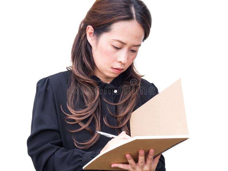 Azjatycki biznesowej kobiety writing na brąz książce nad bielem odizolowywa półdupki fotografia stock