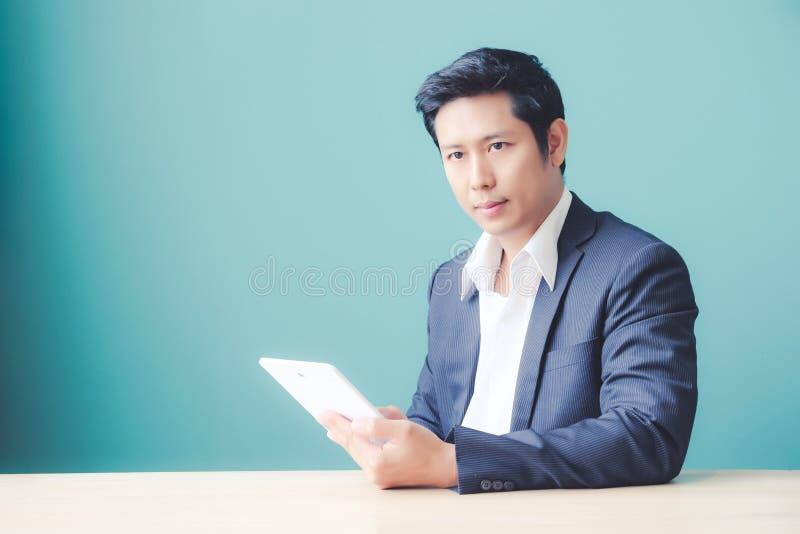 Azjatycki biznesowy mężczyzna używa cyfrową pastylkę przy biurem podczas gdy siedzący obrazy royalty free